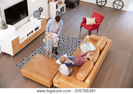 Overhead Shot Of Parents Playing With Children In Lounge