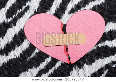Love and relationship concept. Part of pink broken paper heart glued with plaster close up. Valentine card on black and white zebra pattern background.