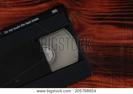 Old retro video tapes over red wooden background.