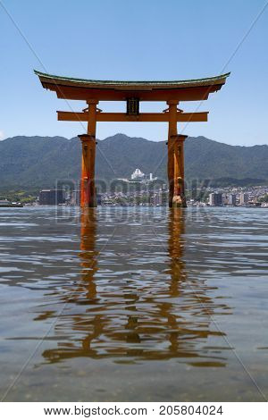 Miyajima - Japan, May 26, 2017: Red Torii gate of the Itsukushima Shrine in the sea near Miyajima