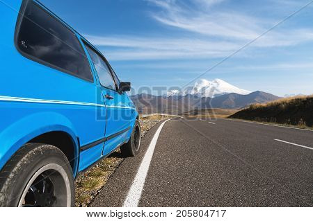 High mountain landscape with a blue car on the roadside. North Caucasus. View of the side of the car which goes to the side of the volcano Elbrus