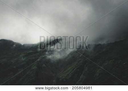 Dense grey fog and cloud shrouding the top of a high mountain summit with steep valley in a sombre alpine landscape
