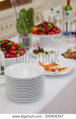 Pile of white plates on catering buffet