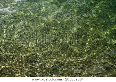 Up view crystal transparent fresh river sea water with stones, free space