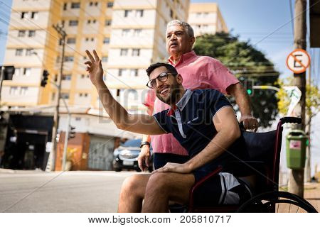 Dad and his son sitting in his wheelchair waiting for the bus