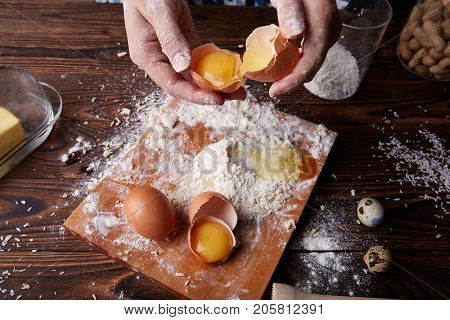 View from above of hands cracking and holding an egg on a baking table background. Desk with white flour and egg yolk for dough.