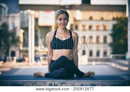 Beautiful sporty fit yogini woman practices yoga asana Cow Face pose gomukhasana in the city
