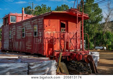 An amazing old red caboose sitting in the parking lot of a business near Lyons Colorado it still looks like it will roll.