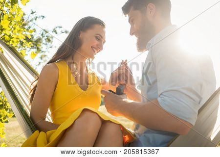 Low-angle view of a happy young man putting an engagement ring on the finger of his girlfriend, after accepting his proposal while sitting together on a hammock in a sunny day of summer