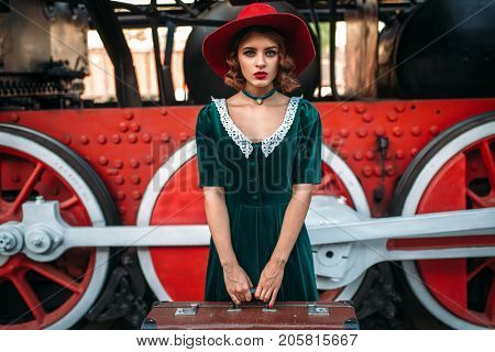 Woman with suitcase against steam locomotive