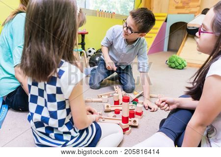 Cute pre-school boy cooperating with his colleagues at the construction of a structure made of wooden toy blocks, under the guidance of a young kindergarten teacher