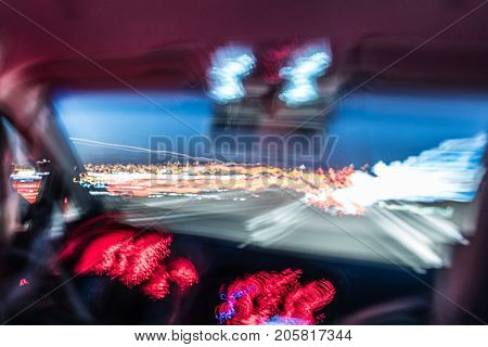 Abstract inside car view on highway at dusk; Concept for extremely high speed, car crash, time travel or dizziness while driving