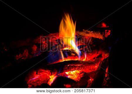 flame on hot embers in dark