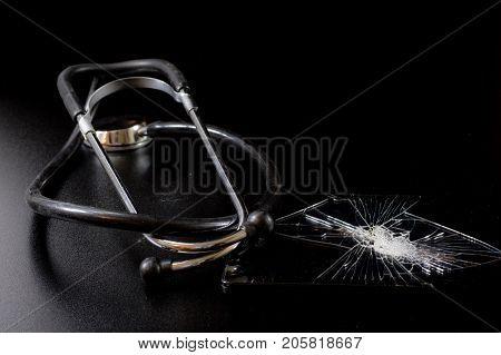 Broken Tablet With Broken Screen And Stethoscope In Repair. Black Table.