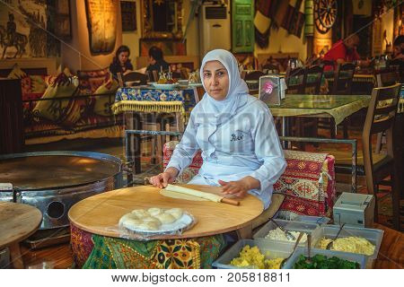 ISTANBUL TURKEY - MAY 2 2017: Turkish woman rolls the dough for preparing traditional Turkish pastries - gozleme on a stove. At restaurant