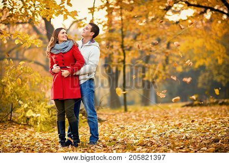 Girlfriend with boyfriend embraced walking in park in autumn