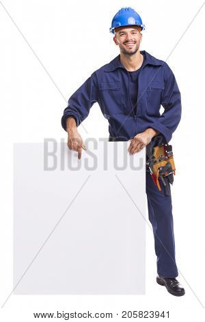 Smiling young worker holding a white placard ready for your text or product