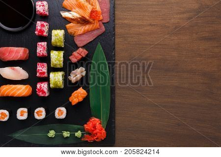 Japanese restaurant, sushi roll platter top view on black rustic wood background and black slate plates. Set with chopsticks, ginger, soy, wasabi. Copy space.