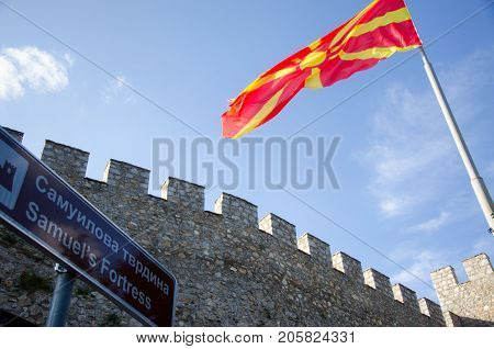 Walls and towers of medieval fortress with waving Macedonian flag on pole and signboard with label Samuel's Fortress, Ohrid, Macedonia