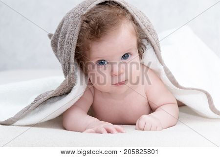 Cute newborn baby girl with beautiful blue eyes on a white terry coverlet. Adorable baby looking out under a white blanket or towel. Happy baby infant in towel after bathing in living room.