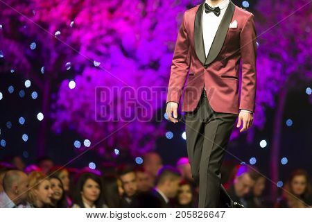 Sofia, Bulgaria - 23, March 2017: A male model walks the runway in stylish modern business during a Fashion Show. Fashion catwalk event showing new collection of clothes.