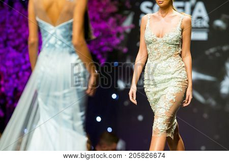 Sofia, Bulgaria - 23, March 2017: A female model walks the runway in stylish green with flowers dress during a Fashion Show. Fashion catwalk event showing new collection of clothes.