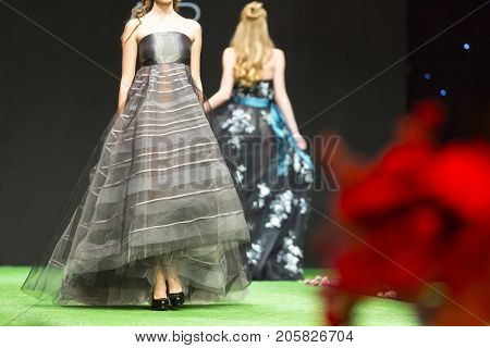 Sofia, Bulgaria - 23, March 2017: A female model walks the runway in beautiful grey dress during a Fashion Show. Fashion catwalk event showing new collection of clothes.