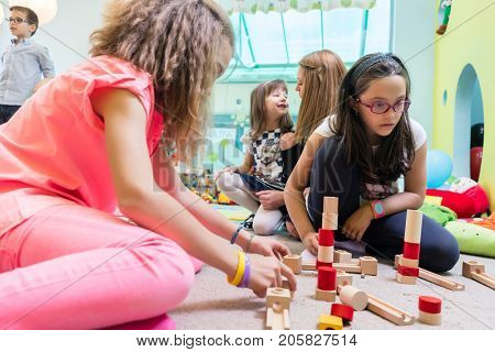 Low-angle view of a cute girl wearing eyeglasses while using wooden toy blocks for building a difficult structure, in balance during playtime at the kindergarten
