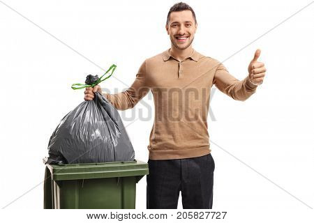 Young man throwing out the trash and making a thumb up gesture isolated on white background