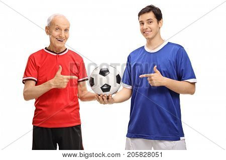 Elderly soccer player and a young soccer player holding a football and pointing isolated on white background
