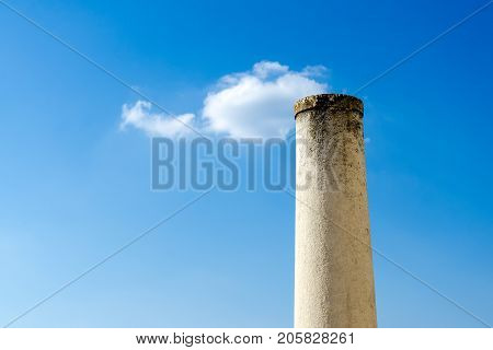 False perspective of stone column with small puffy cloud on top against blue sky