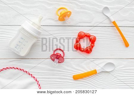 preparation of mixture baby feeding with infant formula powdered milk and bib on white wooden background top view