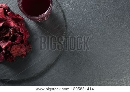 Overhead view of juice with beetroot on plate over slate