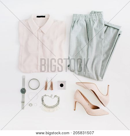 Women modern fashion clothes and accessories. Flat lay female casual style look with pastel blouse trousers high heels watch perfume necklace earrings. Top view.