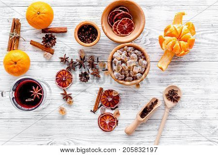 Ingredients of hot mulled wine or grog set with spices and citrus for winter evening. Christmas and new year eve. Light wooden background top view.