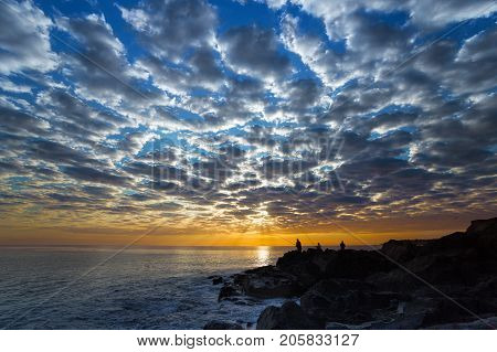 Sunrise. Beautiful dawn sky with clouds over the sea. Silhouettes of fishermen on a stony seashore at dawn.