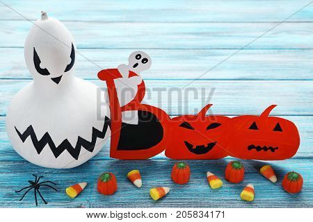 Halloween Pumpkin With Candies On Blue Wooden Table
