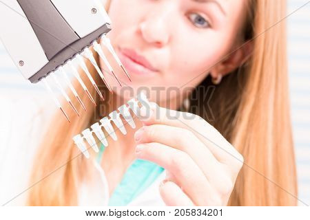 The lab technician examines the results of biochemical tests using a pipette