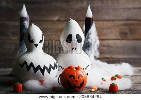 Halloween pumpkins with candies on grey wooden table