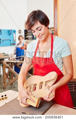Trainee of luthier grinds new guitar part with abrasive paper