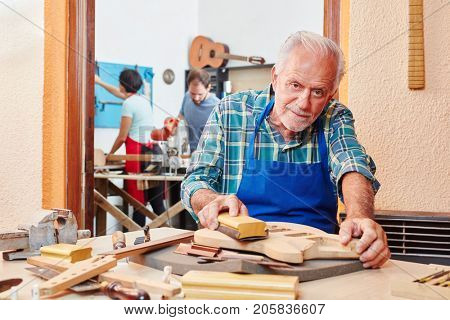 Senior luthier master prepares wood guitar with abrasive paper
