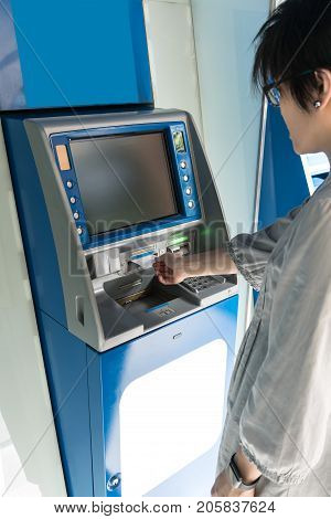 Asian woman looking at monitor screen while pulling carbon paper slip from the blue ATM machine.