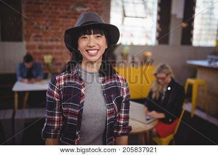 Portrait of smiling young woman wearing hat standing at coffee shop