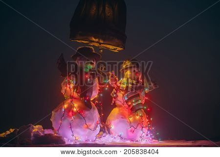 Snowmen couple Christmas. Snowman show with garlands Christmas decorations for New year holiday decorations. Merry Christmas and happy New Year. Color light bulbs and winter clothes frost and snow