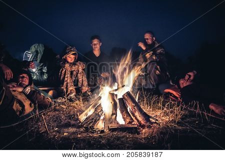 Group of people explorers resting  by the fire in outdoors camp after long hiking day in the night