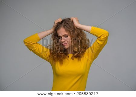 beautiful curly young woman in yellow clothes clings to one's head for vexation on a gray background