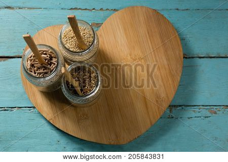Jar with various breakfast cereals on heart shape wooden board