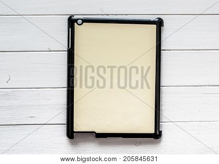 Black tablet Cover for your design or text on a white wooden table Black tablet Cover for your design or text on a white wooden table.