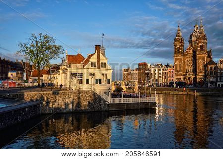 AMSTERDAM, NETHERLANDS - MAY 9, 2017:  Tourist information center, Amsterdam canal and Church of Saint Nicholas (Sint-Nicolaaskerk) on sunset. Amsterdam, Netherlands