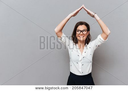 Happy woman in eyeglasses and business clothes hiding under hands like home over gray background